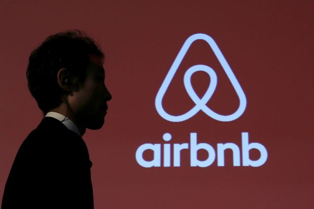 A man walks past a logo of Airbnb after a news conference in Tokyo, Japan, Nov 26, 2015. (Reuters photo)