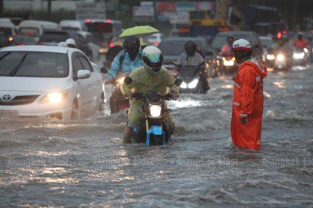 Traffic moves at a snail's pace on flooded Srinakarin Road in Bangkok on Wednesday morning. (Photo by Somchai Poomlard)