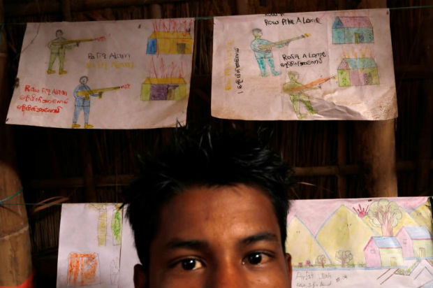 Rafiq Alom, a 14 year-old Rohingya refugee child, stands in front of his drawings of Myanmar soldiers shooting at his village, at Kutupalong refugee camp, near Cox's Bazar, Bangladesh Jan 3, 2018. (Reuters photo)