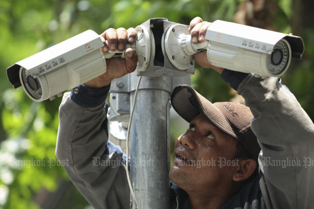 A worker checks and adjusts security cameras installed on a roadside in Bangkok. The government plans to link more than 367,0000 such cameras in a nationwide network in the interests of security. (File photo)