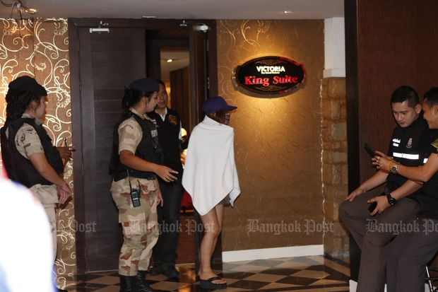 Officials escort a woman from Victoria's Secret massage parlour during the raid in Bangkok on Friday. (Photo by Pattarapong Chatpattarasill)