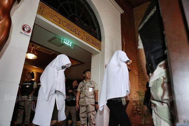Detained women emerge from the massage parlour where police and other favoured persons got free drinks, food and 'service' so long as the massage parlour was protected. (Bangkok Post file photo)