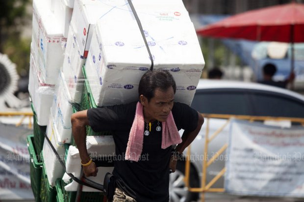 A Bangkok labourer struggles with a large load. Workers and employers both are expressing opposition to a new schedule for minimum wages, due to take effect April 1. (File photo by Pawat Laopaisarntaksin)