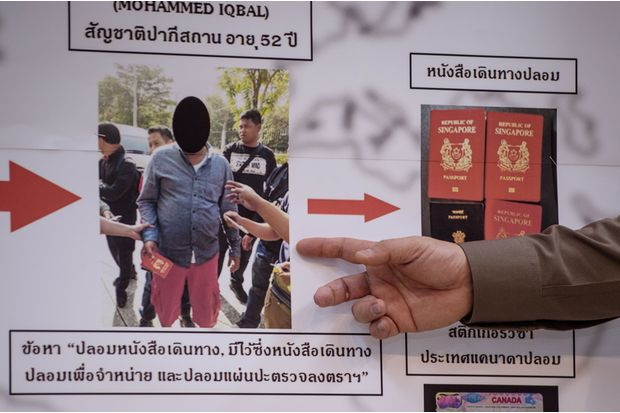 Lt Gen Suttipong Vongpint (right), commander of the Immigration Bureau, points to a board with information about an apprehended passport forger during a press conference in Bangkok on Friday. (AFP photo)