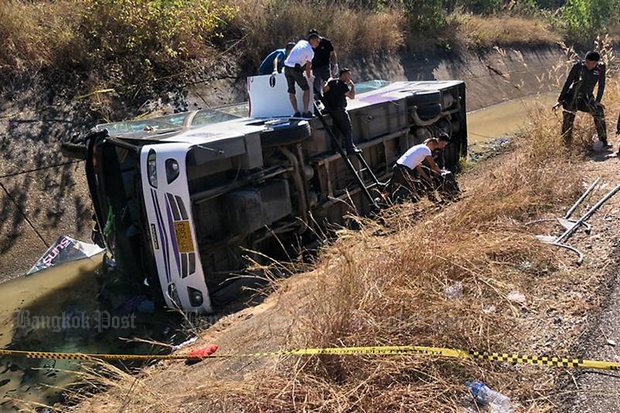 A tour bus lies overturned in Chiang Mai province in an accident which injured dozens of tourists in December. (Bangkok Post file photo)