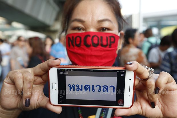 A demonstrator shows a 'Time's up' sign on her mobile phone at a rally against the junta's power succession and election delay at the BTS skywalk in Pathumwan district on Saturday. (Photos by Pattarapong Chatpattarasill)