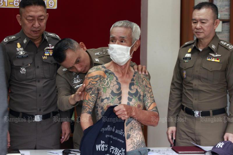 Police look at Shigeharu Shirai's tattoos at Muang police station in Lop Buri after the Yakuza gang member was arrested on Jan 10, 2018. (Photo by Pornprom Satrabhaya)