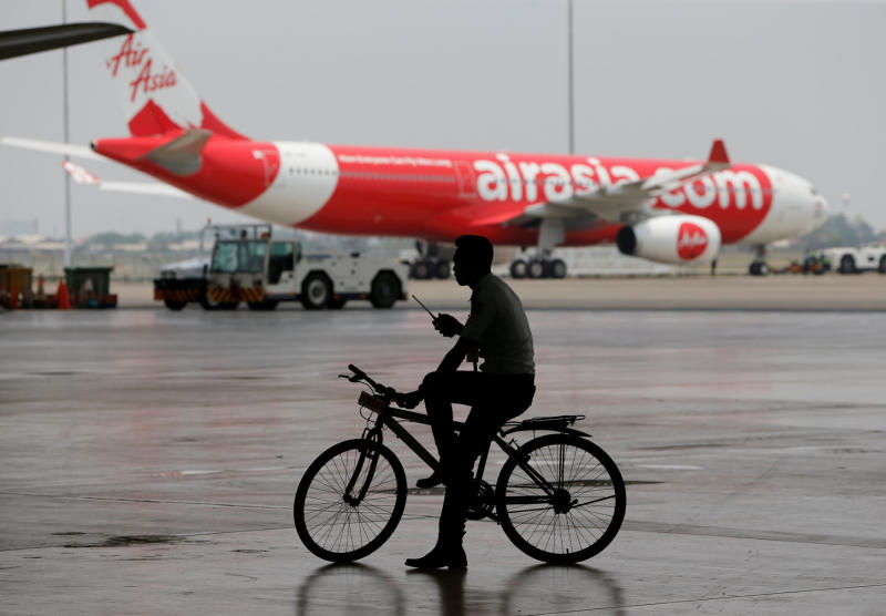 A security guard rides a bicycle past an AirAsia plane at the Garuda Maintenance Facility AeroAsia in Tangerang, Indonesia, on Sept 20, 2017. (Reuters photo)