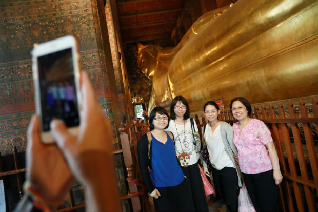 Chinese tourists take pictures inside a temple in Bangkok, Thailand on Monday. (Reuters photo)