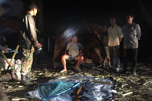 A park ranger stands guard over Italian-Thai Development Plc president Premchai Karnasuta, sitting, and the other suspects at their hunting camp in Thungyai Naresuan Wildlife Sanctuary in Kanchanaburi province. (Photos supplied by Piyarach Choncharoen)