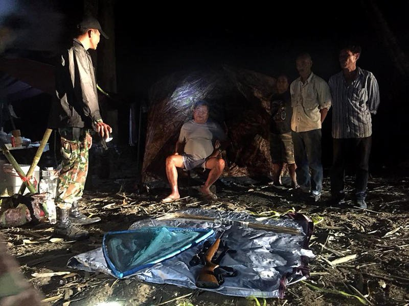 Found in a no-camping zone with guns and animal carcasses, Mr Premchai (seated) denied he was camping and hunting illegally and is free on token bail. (Photo provided by state officials)