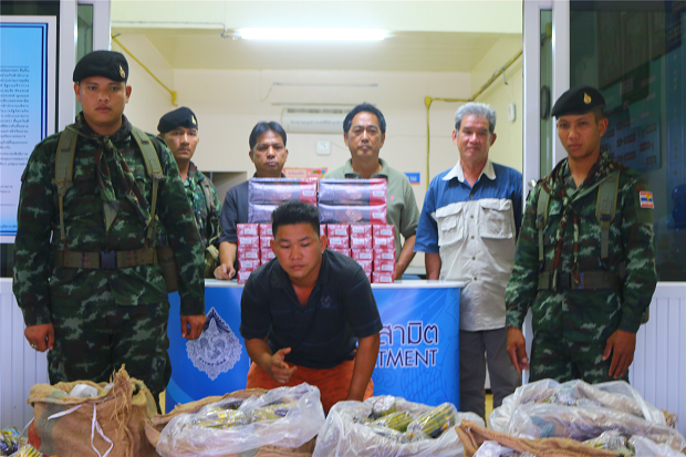 Contraband foreign cigarettes and tobacco seized from the pickup truck carrying them from the Myanmar border in Kanchanaburi's Sangkhla district. The driver (centre) was arrested. (Photo by Piyarach Chongcharoen).