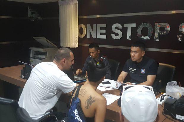 Jose Polanco Jr (in white T-shirt) talks to Pattaya police at the police station on Monday. (Photo by Treenai Chansrichol)