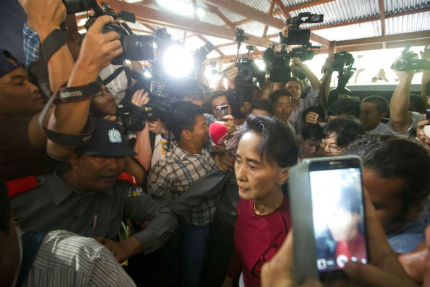 In this Nov 8, 2015 file photo, Myanmar's National League for Democracy party leader Aung San Suu Kyi is crushed by the media as she arrives at a polling station to vote in Yangon, Myanmar. (AP photo)