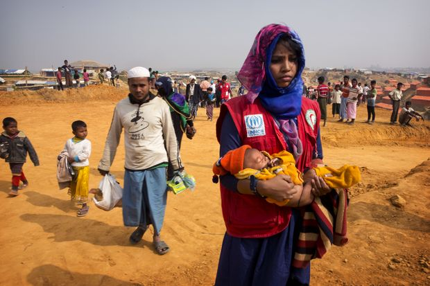In this Jan 14, 2018 photo, a volunteer carries a malnourished child from a newly arrived Rohingya family to a transit camp in the Kutupalong refugee camp near Cox's Bazar, Bangladesh. (AP photo)
