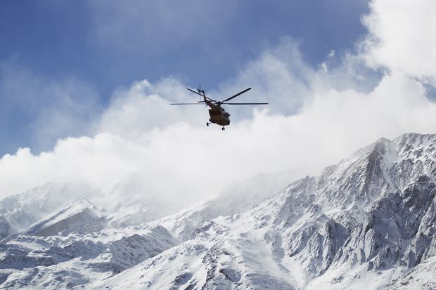 In this photo provided by Tasnim News Agency, a rescue helicopter flies over the Dena mountains while searching for the wreckage of a plane that crashed on Sunday, in southern Iran, on Monday. (Ali Khodaei/Tasnim News Agency via AP)