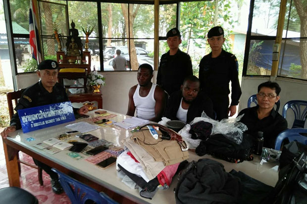 The two Nigerians are questioned by rangers of the Rong Kluea task force who caught them attempting to flee in a taxi after being spotted in the border market in Aranyaprathet district of Sakaeo province on Monday. They were charged with illegal entry.(Photo by Sawad Ketngam)