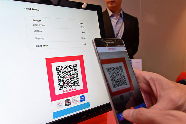 A consumer making an e-commerce transaction using the NETS QR code in Singapore. (TODAY photo)