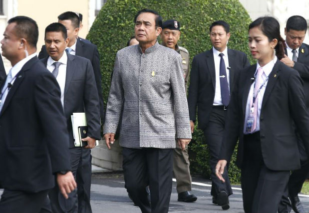 Prime Minister Prayut Chan-o-cha (centre) arrives for a weekly cabinet meeting at the Government House in Bangkok on Tuesday. (EPA photo)