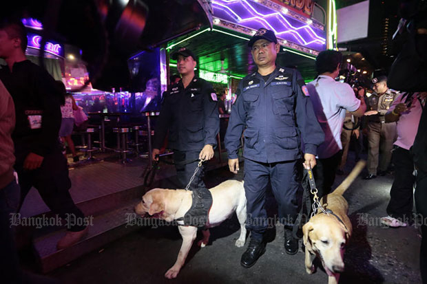 Police pace through tourist-crowded Soi Cowboy in Bangkok during an inspection early on Wednesday, part of a nationwide operation against foreigners staying illegally and working in Thailand. (Photo by Patipat Janthong)