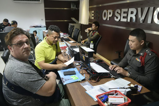 Henrik Christian Koch (left), 49, files a complaint after almost 100,000 baht was allegedly withdrawn from his bank account at the Pattaya police station in Chon Buri province on Friday. (Photo by Chaiyot Pupattanapong)