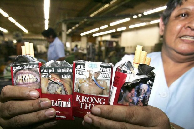 A worker holds sample packets of the Thai Tobacco Monopoly's most popular brand. A new excise tax structure will likely cost the TTM losses of around 1.5 billion baht. (EPA file photo)