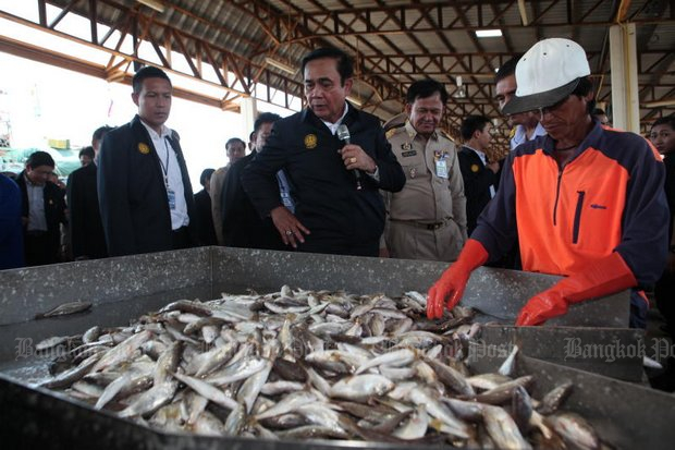 Prime Minister Prayut Chan-o-cha narrates the actions of a fish sorter as he takes the issue of illegal fishing into the heart of the industry at the Fish Marketing Organisation's office in Samut Sakhon on Monday. (Photo by Apichart Jinakul)