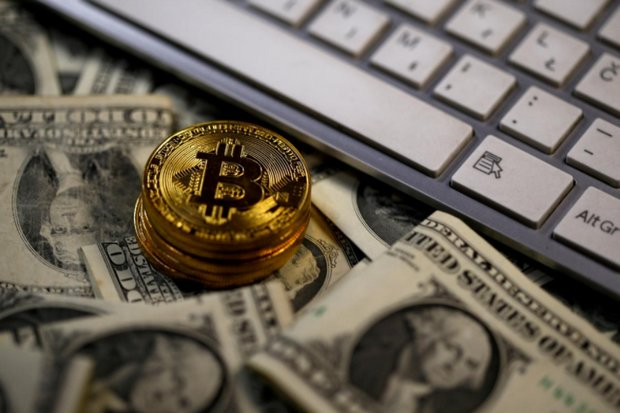 Bitcoin (virtual currency) coins placed on US dollar banknotes. (Reuters file photo)