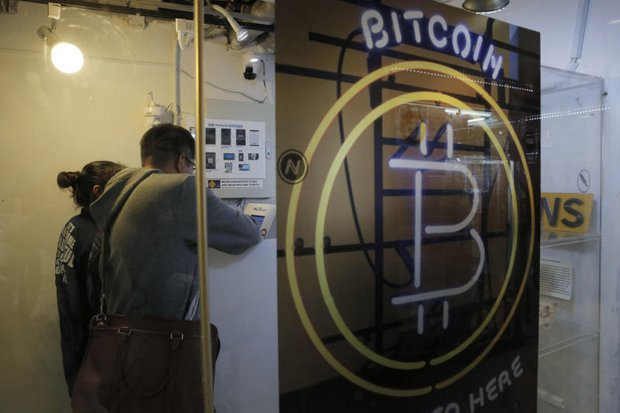 People use a bitcoin ATM in Hong Kong. Regulations are being quickly drawn up that will allow Thailand to start to catch up with economies where cryptocurrencies already are common. (AP file photo)