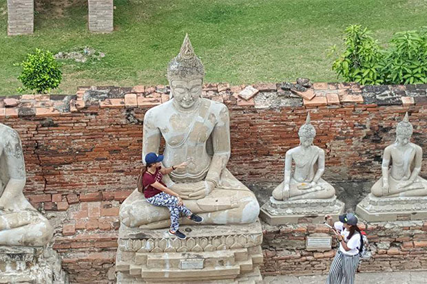 A tourist poses for pictures in the lap of a large Buddha statue at Wat Yai Chai Mongkol in Ayutthaya. (Photo by Sahai Phordam via @queentogtherriseone's Facebook page)