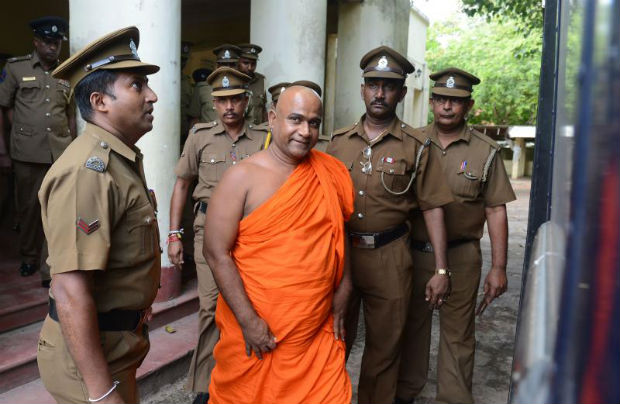 Sri Lankan guards escort Buddhist monk Akmeemana Dayarathana (centre) after he was remanded in custody in Colombo on Oct 2, 2017, over his involvement in a violent attack on Rohingya refugees. The monk is accused of leading a violent attack on a UN-protected refugee centre at the Colombo suburb of Mount Lavinia and forcing the removal of 31 Rohingya, including 16 children, to a safer location.  (AFP photo)