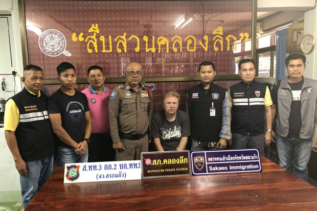 Dariusz Pieprzyca, seated, at Klongluek police station in Sa Kaeo. He is wanted on an arrest warrant for theft issued by the Roi Et Provincial Court and also wanted by Polish police. (Photo by Sawad Ketngam)