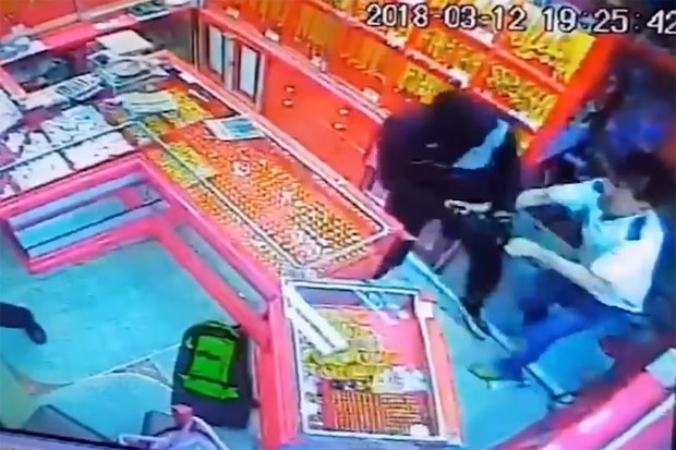 The picture captured from security camera footage shows the male robber fighting with the gold shop owner in Nong Chang district, Uthai Thani, on Monday night.