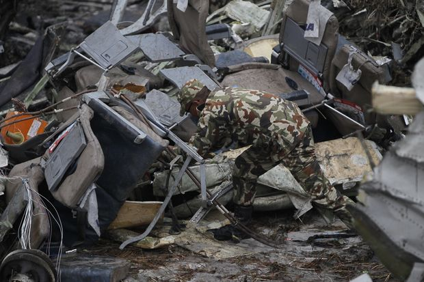 A Nepalese rescuer searches amid the debris after a passenger plane from Bangladesh crashed at the airport in Kathmandu on Monday. (AP photo)