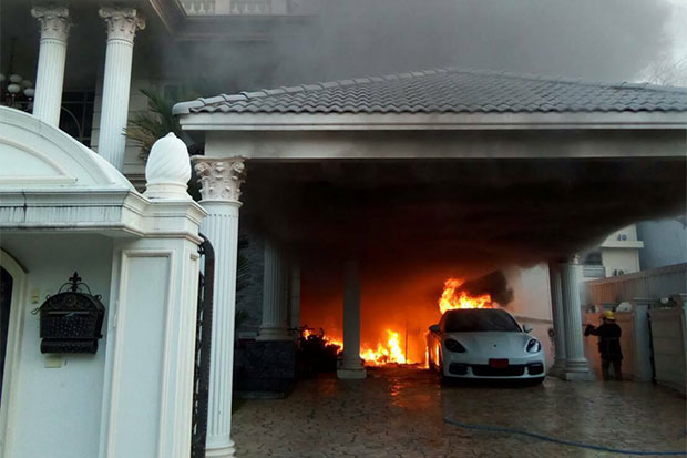 The Porsche Panamera catches fire as firefighters reach the house on Friday. (Photos from @ThaiRescueNews Facebook)