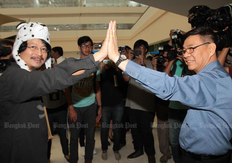 Sombat Boonngamanong, left, is congratulated by former election commissioner Somchai Srisutthiyakorn at the Election Commission office when he applied to register the Grin Party. (Photo by Tawatchai Kemgumnerd)