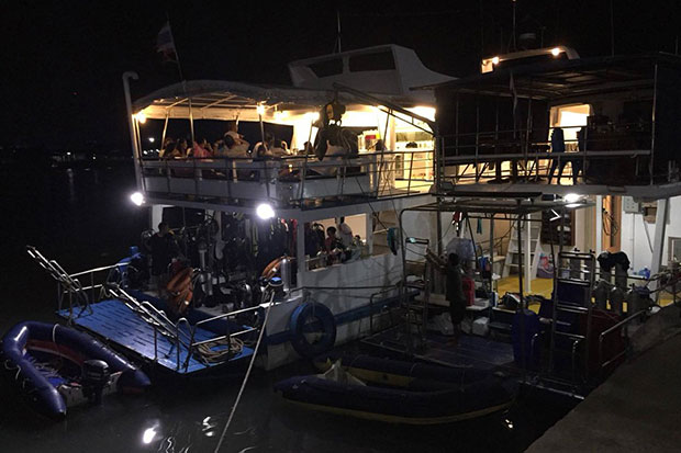 Thirty-six scuba divers and crew members rest on the 'Scuba Net' boat on Sunday after their own boat, the 'Choltara', caught fire and sank off the Andaman coast in Krabi. (Photo from @K5_Rescue Twitter account and Krabi's disaster prevention and mitigation office)