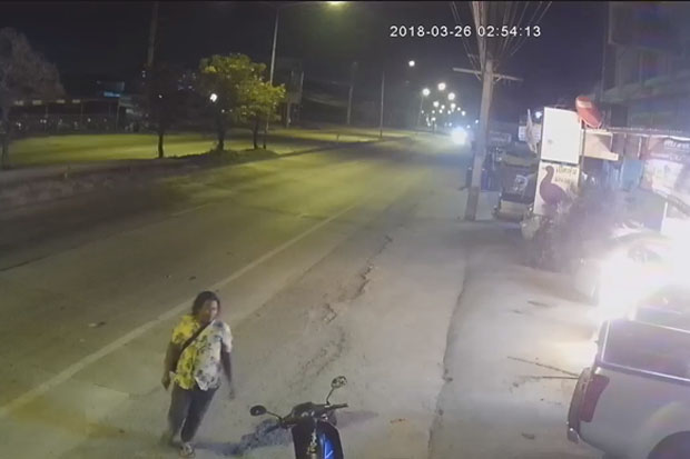 The man is seen walking to his motorcycle after setting fire to a vehicle in Phan Thong district, Chon Buri, early Monday morning. (Photo captured from a video clip from Facebook user Chatchai Surin)