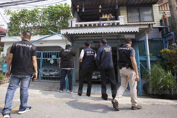 Officials enter the twin townhouses of C8 education official Rojana Sinthi in Don Muang district on Friday. On Monday she was sacked from the civil service for  corruption, losing all benefits. (Photo by Apichit Jinakul)