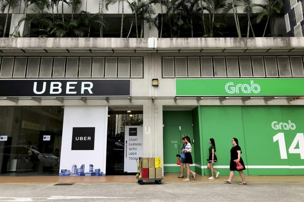 Office workers walk past Grab and Uber offices on Monday. Uber will disappear after April 1. (AP photo)
