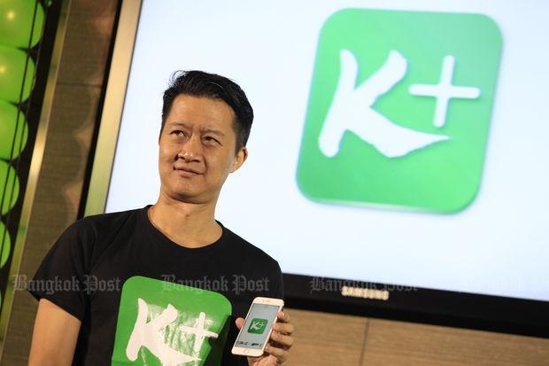 KBank senior executive vice-president Pachara Samalapa shows K Plus mobile app during its launch on May 8 last year. (Bangkok Post file photo)