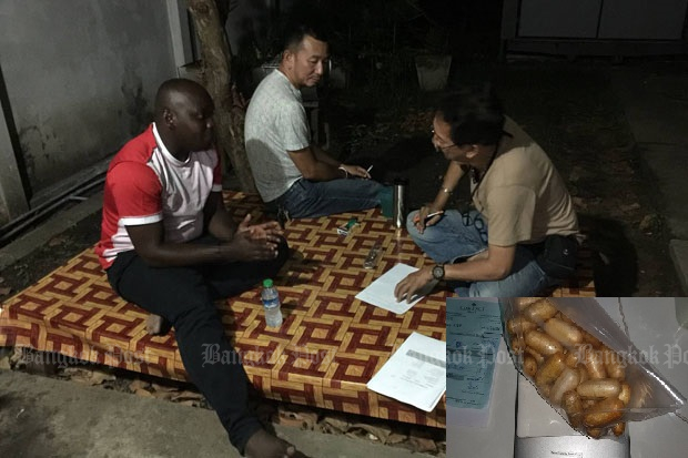Officers talk to Nindi Sefu Burhani, a Tanzanian national, during his arrest for possession of 671 grammes of cocaine found in a toilet wastebin in his hotel room in Bangkok on Tuesday. (photo by Wassayos Ngamkham)