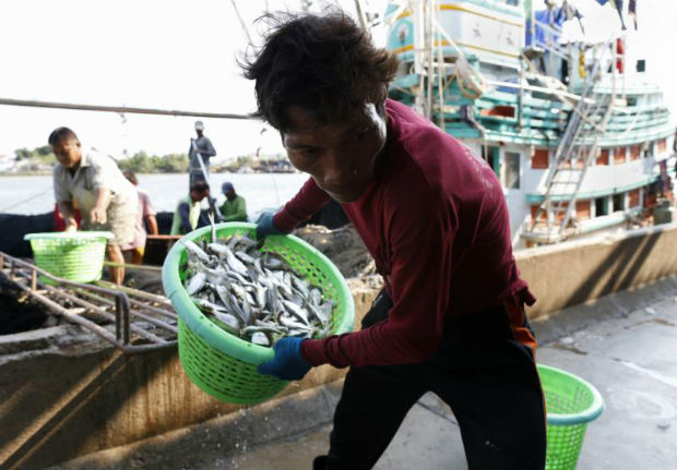 Myanmar migrant fishermen unload fish from a Thai fishing boat at a port in Samut Sakhon province, March 19, 2018. (EPA photo)