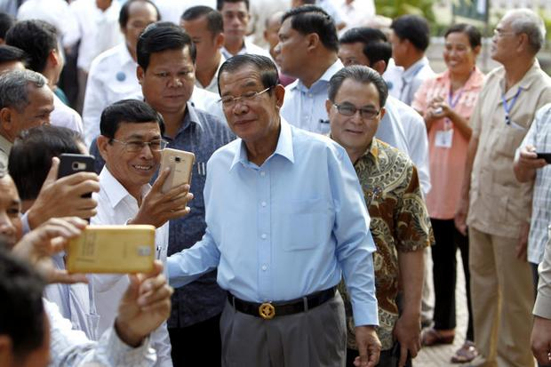 Cambodian Prime Minister Hun Sen, chief of the ruling Cambodian People's Party, poses for a selfie with party supporters after voting in the senate election at Takhmau polling station in Kandal province, southeast of Phnom Penh, on Feb 25. (AP photo)