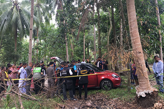 Police cordon off the area where a 34-year-old woman and her teen daughter were found dead inside their car in a field of coconut trees in Nakhon Si Thammarat on Tuesday morning. (Photo by Nujaree Raekrun)
