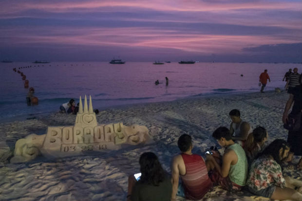 Visitors at White Beach on Boracay, a Philippine island that has rapidly become a major travel estination, March 28, 2018. President Rodrigo Duterte has ordered that Borocay be closed to tourists for six months, citing a need to clean up the island's overtaxed sewage treatment systems. (Jes Aznar/The New York Times)