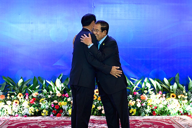 Cambodian Premier Hun Sen embraces Prime Minister Prayut Chan-o-cha during the opening of the Mekong River Commission summit in Siem Reap on Thursday. (Government House photo)