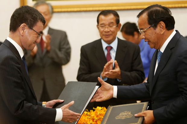 Japan's Foreign Minister Taro Kono (left) exchanges a document with his Cambodia's counterpart Prak Sokhonn as Cambodia's Prime Minister Hun Sen (centre) applauds after a signing ceremony in Phnom Penh on Sunday. (Reuters photo)
