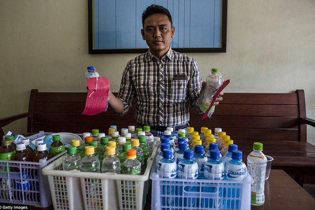 A policeman shows bottles of illicit alcohol seized from black market dealers. (File photo)