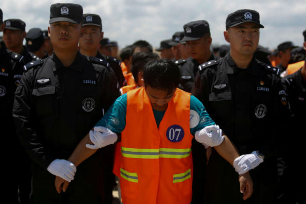 Chinese nationals (in orange vests) who were arrested over a suspected internet scam are escorted by Chinese police officers before being deported at Phnom Penh International Airport, in Phnom Penh, Oct 12, 2007. (Reuters file photo)
